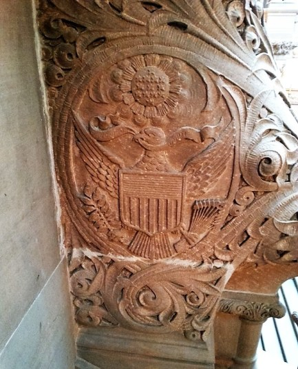 A close-up of a carving in the stone of the staircase. The entire staircase is covered in elaborate carvings included historical figures for both NY and US history.