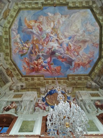 This is a ceiling mural in the Marble Room of the Upper Belvedere. The artist was Carlo Carlone and he worked on this from 1721 - 1723. Remember that description on how Baroque art and architecture can give that sense of infinity, that's seen here since the sky seems to not really end; an idea that it goes beyond the borders. Also bright colors, so many colors! Also, it may look like your looking at walls below the ceiling that are carved. They are not. It's all painting that gives off the look of depth and that sculpted, opulent look.