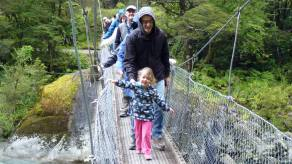 Child leading the way across a suspension bridge at a scenic stop with Fiordland Tours, along road to Milford Sound