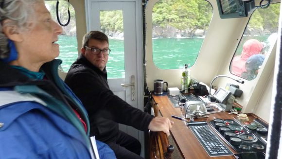 Captain and guest in the bridge of Cruise Milford's Milford Adventurer sightseeing boat tour