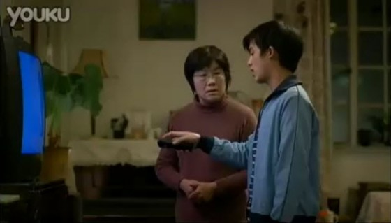 Tencent 2011 Chinese New Year Advertisement: Son teaches mother how to use television remote control.