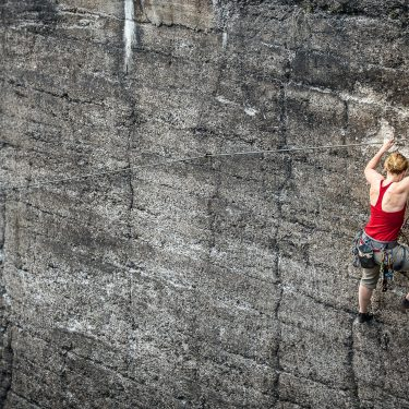Woman using strength to climb up rocky cliffe