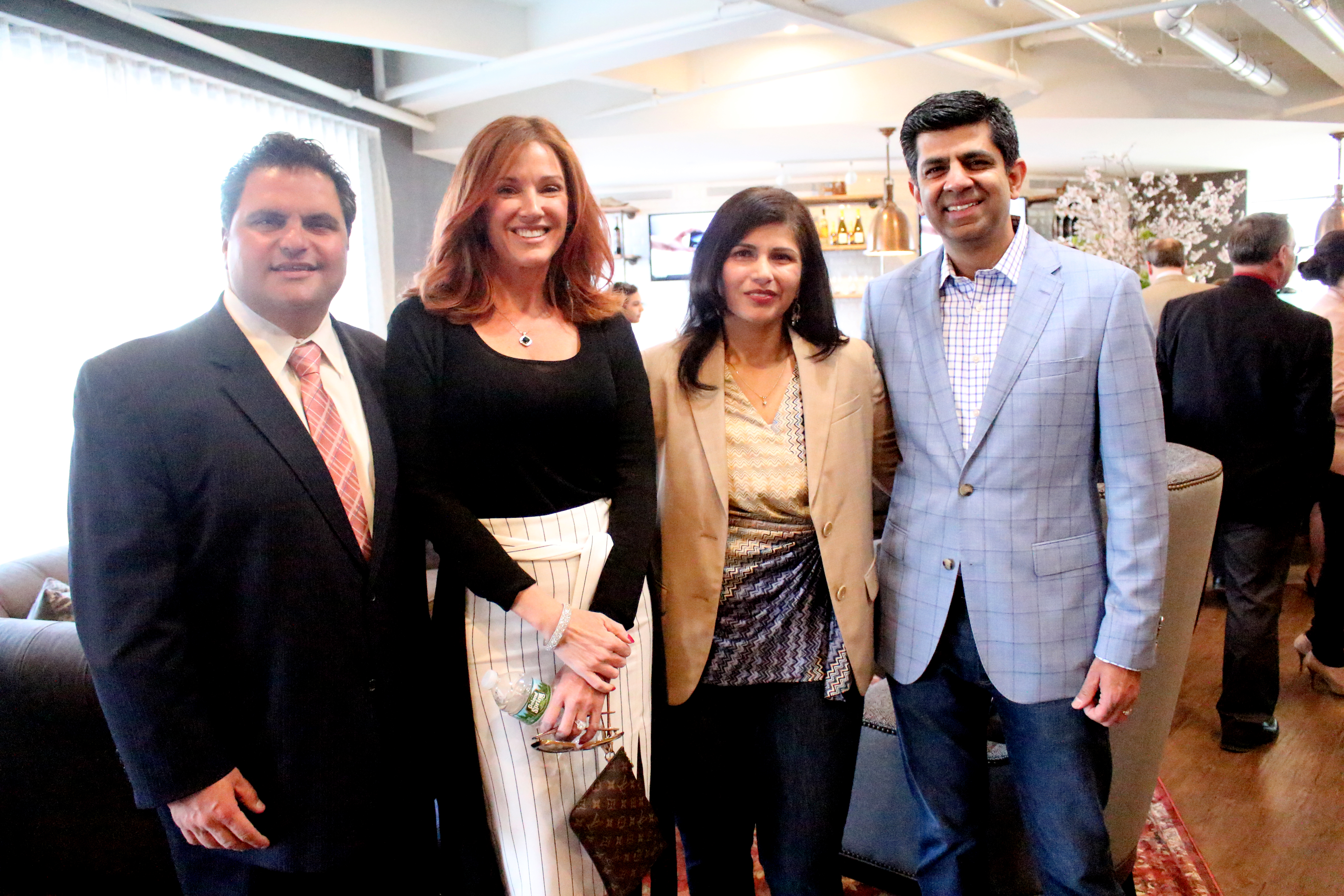 "City ""enVisions"" bright future as first hotel opens --- A VISION COME TRUE: Mayor Carlo DeMaria and his wife, Stacy, are shown with Global Vision Hotels President Gautam Sharma and Principal/Senior Vice President Revenue Development Shikha Talwar at the ribbon-cutting ceremony for enVision Hotel Everett on Monday, April 10. -- A boutique hotel featuring 101 rooms, its design, which was developed by Jessica Smith, evokes the history of Everett and the 95-year-old building's past as a shoe factory – from the front desk and a stack of vintage suitcases to design elements like old maps and sewing machines. The hotel also features a café, lounge and 1,300 sq. ft. meeting room on the ground floor able to accommodate about 50 people. A separate building connected to the hotel will feature a fitness center."