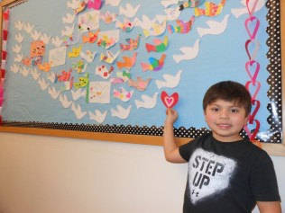 "A LOVE NOTE TO HEAVEN: Anthony Sazo, 6, displays a special Valentine's Day heart he crafted for his great-grandmother, Rose DiMinico, who passed away in September 2016. He had the heart stapled to the Peace display on the bulletin board at Saugus Public Library, which already featured doves to celebrate ""Love, Peace and Joy."" (Saugus Advocate Photo by Mark E. Vogler)"