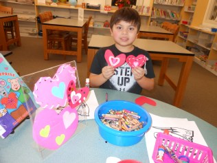 A PAIR OF HEARTS: Six-year-old Anthony Sazo of Lynnfield makes a Valentine's Day heart for himself and one for his late great-grandmother this week at the Saugus Public Library (Saugus Advocate Photo by Mark E. Vogler)