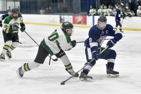 Tyler Murphy of Lynnfield keeps control of the puck as he is pressured by a Pentucket-Georgetown player during their game at the McVann-O'Keefe Rink in Peabody on Tuesday, Feb. 20, 2018.