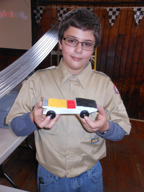 """A FATHER-SON SPECIAL: Billy Ferringo, of Saugus Boy Scout Troop 62, showed off the car his dad, Bill, made and used in his Cub Scout Pinewood Derby 30 years ago. Billy used the car – known as """"Weasel"""" – to run in the """"open race"""" for non-Cub Scouts during Saugus Cub Scout Pack 62's Annual Pinewood Derby last Saturday. (Saugus Advocate photos by Mark E. Vogler)"""