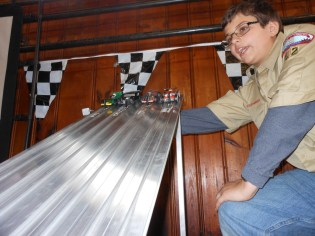 THE RACE IS ON! Billy Ferringo, of Saugus Boy Scout Troop 62, is poised to pull the lever that launched the first heat of 27 cars that raced Saturday morning in the basement of the Cliftondale Congregational Church during Saugus Cub Scout Pack 62's Annual Pinewood Derby. See story and more photos inside. (Saugus Advocate Photos by Mark E. Vogler)