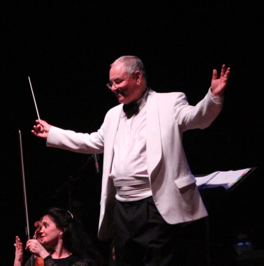 Orchestra conductor Neil Grover acknowledges the audience.