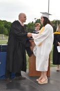 School Committee Chair Jamie Hayman presents a diploma to Emory Caswell.
