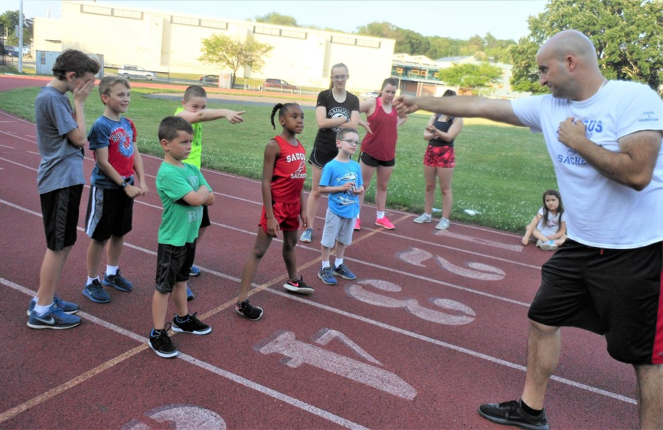 POINTING TO SUCCESS: Christopher Tarantino, right, points to a group of young athletes this week at Belmonte Middle School, where he is overseeing the 2018 Saugus Sachems Summer Track Camp, which starts next week.