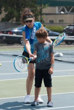 Instructor Susan McAnneny helped Felipe Oliveira's with his form on the tennis court during Tuesday's tennis day in Malden.