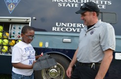 State Police Underwater Recovery Unit member Kevin Baker shows Isiah a swim fin used by his crew.