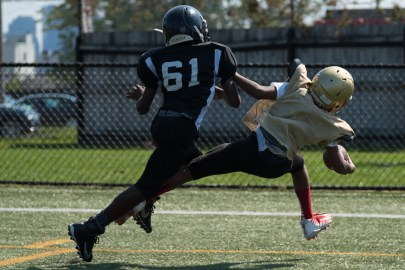 A Cambridge Pop Warner player tackled an Everett player who was determined to keep his grip on the ball.