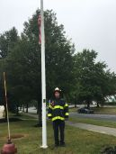 Fire Capt. Rob Fortuna lowers the station flag to half-mast as a symbol of respect to honor the lives' lost during 9/11.
