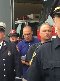 Ret. Fire Lt. James Caramello reads the firefighters' prayer during Tuesday's 9/11 remembrance ceremony as many fire officials close their eyes to pray.
