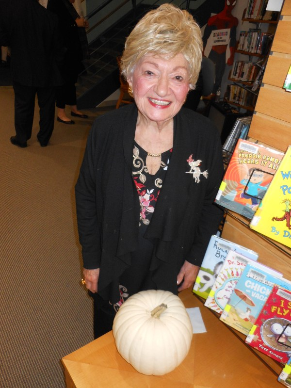 IN THE HALLOWEEN SPIRIT: Ruth Berg, a longtime supporter of the Saugus Public Library and causes in town, admires a white pumpkin while supporting a colorful witch pin on her jacket.