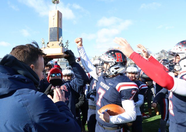 Coach Lou holds the trophy high, as the Patriots beat the Vikings and end the 2018 season with a 7-4 record, the best in 35 years of play.