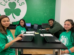 Celtics rookie Rob Willams interacts with students Cindy Nguyen, Margie Martinez Zuninga and Araceli Flores at the robotics lab table.
