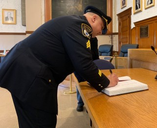 Police Officer John Cannon signs a book, which makes him Police Sgt. John Cannon.