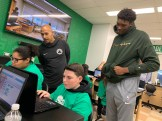 Celtics players Dana Barros and Rob Williams look over the shoulder of students Aliyah Ingram and Anthony Masucci.