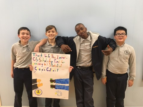 Seventh grade students pose with their poster celebrating the financial aid granted to Cheverus Catholic Students in 2018/19.