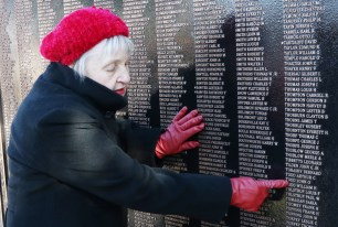 Barbara Tolstrup points to her father and father in law's names on the plaque she helped to unveil at Devir Park during a dedication ceremony Sunday morning honoring 2,821 Malden veterans. (Advocate photo by Al Terminiello)