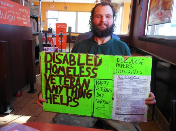 """HIS """"HELP"""" SIGN: Homeless veteran Doncristino J. Racca during an interview this week in the Dunkin' Donuts coffee shop off of Essex Street near Route 1. The U.S. Army National Guard veteran, who served more than a year in Afghanistan, says he uses this sign when he heads out on the streets of Saugus to panhandle or seek whatever kind of help he can find. It includes copies of his veteran's card and honorable discharge papers """"so people will know I'm no fraud."""" (Saugus Advocate Photo by Mark E. Vogler)"""
