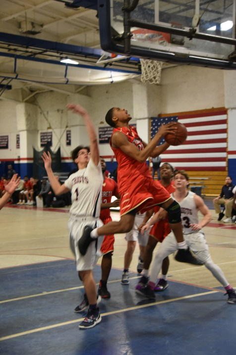 Senior Devin Brito soars over the Revere defenders. (Advocate photos by Ross Scabin)