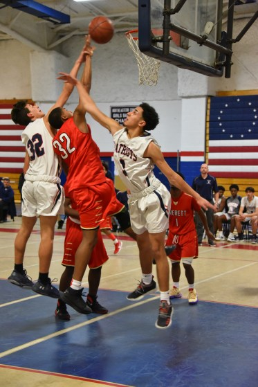 Forward Wilfredo Martinez (32) battles Everett sophomore Kevin Artiste for a rebound while a Pats teammate helps out. (Advocate photos by Ross Scabin)
