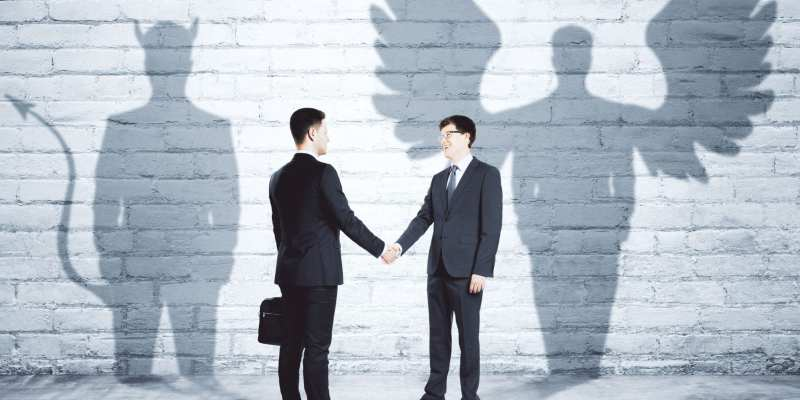 76682773 - businessmen with angel and demon shadows shaking hands in brick interior. team work concept