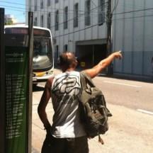 Homem com bolsa nas costa com o braço esticado solicitando para do ônibus que está chegando