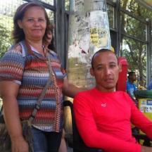 Mulher em pé ao lado do rapaz em sentado de uma cadeira de rodas