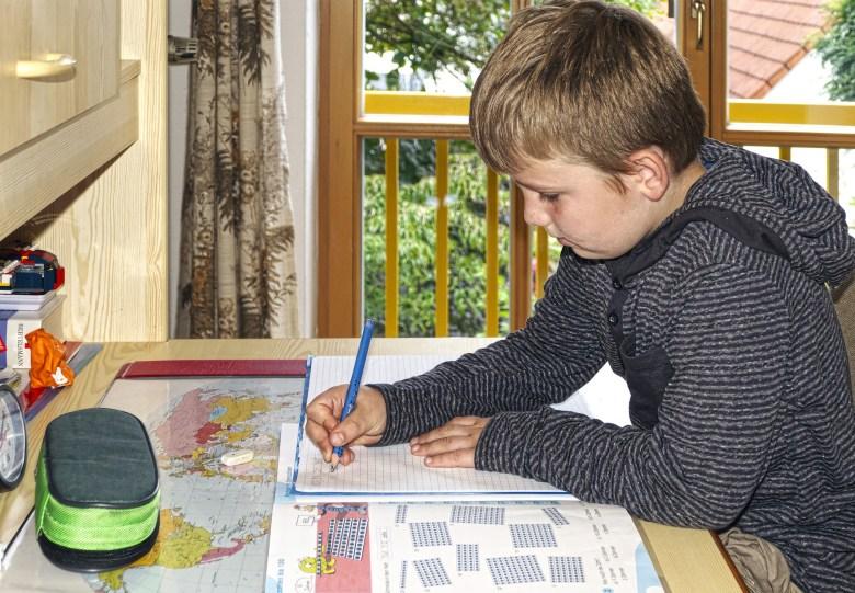 Jeune garçon qui fait ses devoirs à la maison