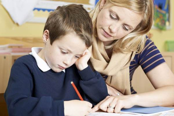 Jeune femme enseignante qui aide un garçon de primaire à résoudre un problème