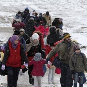 Migrants walk through a frozen field after crossing the border from Macedonia near the village of Miratovac Serbia
