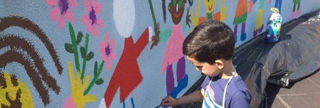 Menino pinta mural da escola