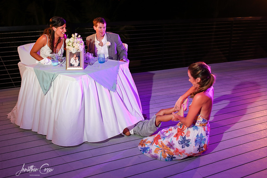 Ring bearer under the sweetheart table. Kids at weddings captured by Jonathan Cossu Photographer
