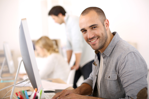 Cheerful guy sitting in front of desktop computer - work environment