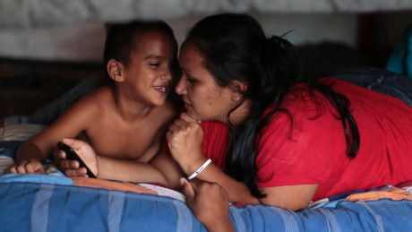 Hispanic Mother & Child bonding on a bed or sofa.