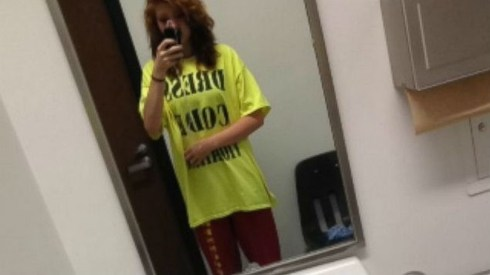 Young Woman taking a 'selfie' of herself wearing a yellow tee shirt with big black letters that say 'Dress Code Violation!""