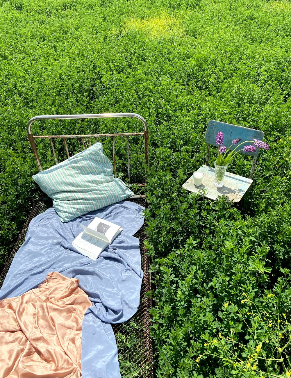 bed with book near chair with flower bunch in field