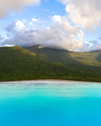 Aerial Over The Blue Ocean To The Epic Cloud Covered Mountains Of The Daintree National Park