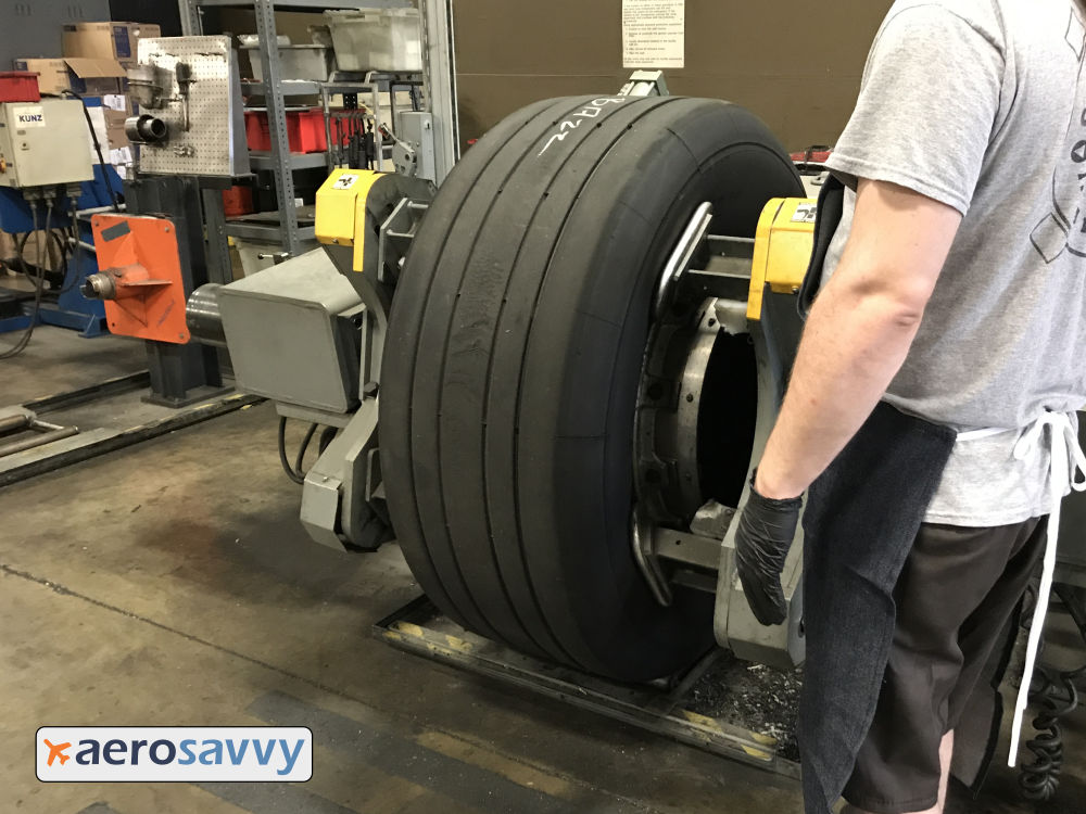 A wheel is positioned vertically. Hydraulic arm squish the tire from both sides to unstick the tire bead from the wheel hub.