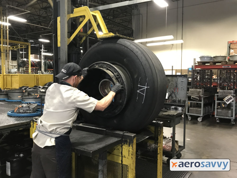 A technician pulls on the wheel rim to remove it from the tire