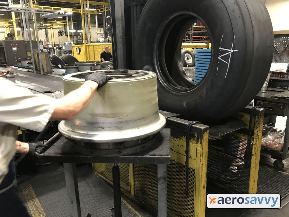 Large inner aluminum wheel rim laying on its side next to tire.