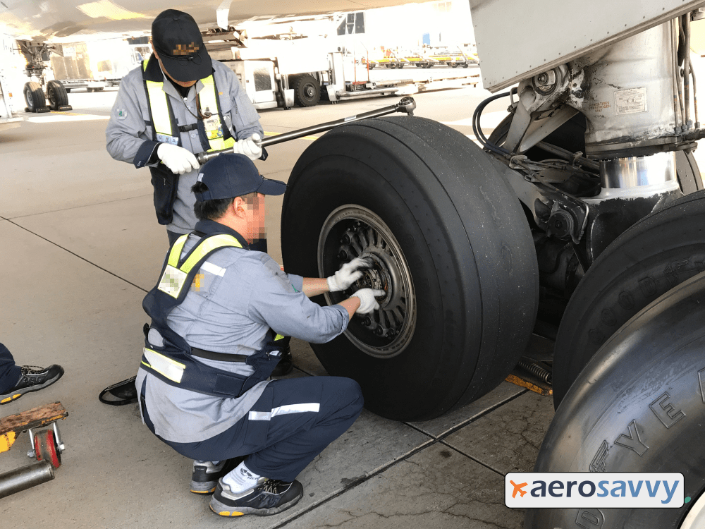 A technician is removing the large axle nut from the center of the wheel. Nut is about the diameter of an adult palm. A second technician stands nearby with a 3 foot long socket wrench.