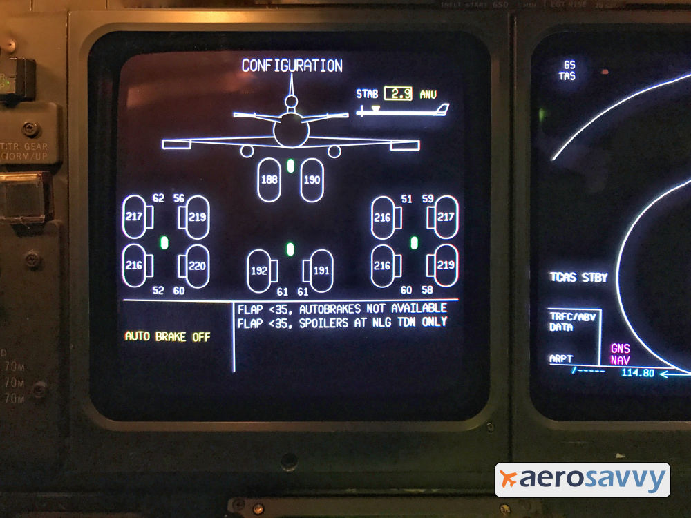 Center CRT display on MD-11 instrument panel. Display shows arrangement of 12 aircraft wheels. Wheels are shown as ovals. Each wheel shows a pressure inside it. 190 pounds for 2 nose wheels and 2 center wheels. 217-219 pounds for 8 main wheels. Smaller numbers below each wheel show brake temperatures (52 to 61 degrees Celsius).