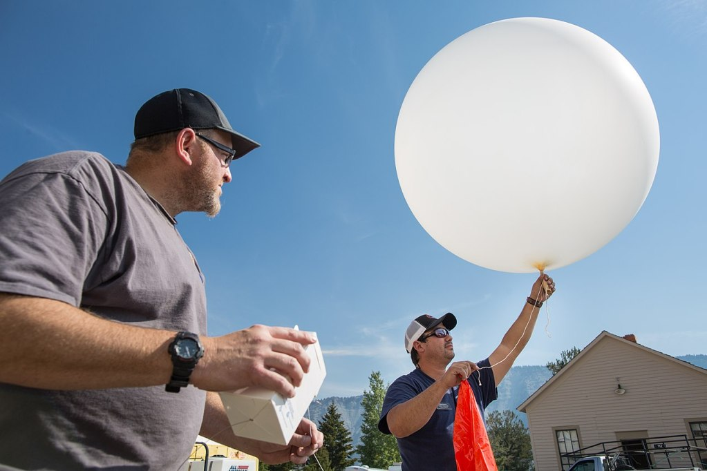 Man holding a 6 foot diameter white balloon. His assistant holding the small white cardboard box radiosonde. Preparing to release the balloon.