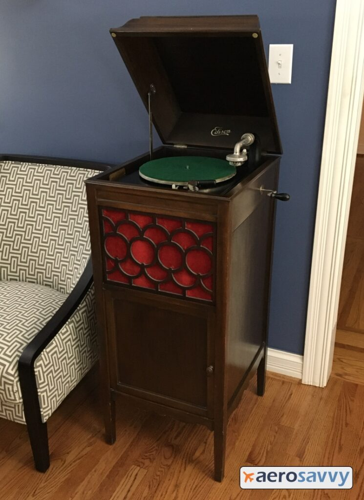 Full view of the Edison player. It's about 4 feet tall, 2 feet wide and 2 feet deep. Door in bottom half to store 25 upright discs. Red cloth grill cloth on upper front behind a decorate wood lattice design.  Nickel plated hand crank sticks out of the cabinet on the right side. Lid opens to reveal green felt covered platter and nickel tone arm.